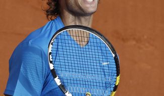 Rafael Nadal of Spain celebrates his victory over John Isner of the US during the first-round match of the French Open tennis tournament at Roland Garros stadium in Paris, Tuesday May 24, 2011. (AP Photo/Christophe Ena)
