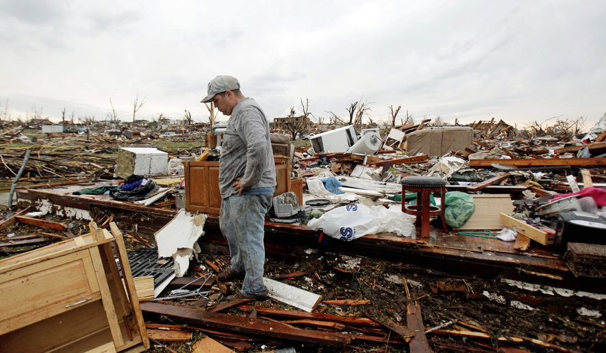 Josh Ramsey looks through the rubble of what is left of his mother-in-law's home Monday after a tornado struck Sunday in Joplin, Mo. The massive twister killed at least 116 people in the area. (Associated Press)