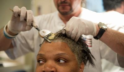 Alexis Carter gets her hair colored at Piaf Salon. A bill to be reintroduced by Rep. Janice D. Schakowsky would give the FDA more regulatory control over beauty products. Many salon workers favor the bill but not manufacturers. (Barbara L. Salisbury/The Washington Times)