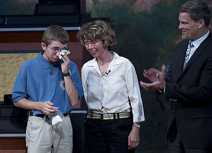 Thirteen-year-old Tine Valencic from Colleyville, Texas, wipes tears from his eyes after winning the 2011 National Geographic Bee in Washington, D.C., on Wednesday, May 25, 2011. His mother, Jana, center, stands by him while National Geographic Society president Tim Kelly, right applauds. Tine beat the other 10 finalists and was the only contestant who did not get one question wrong in the entire bee. He received a $25,000 scholarship, a lifetime membership in the National Geographic Society and an all-expense-paid trip for two to the Galapagos Islands. (Barbara L. Salisbury/The Washington Times)