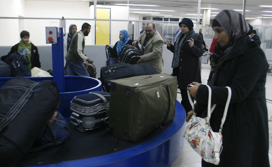 **FILE** In this photo from Feb. 18, 2011, Palestinians collect their belongings as they come back from Egypt at the Rafah border crossing the Gaza Strip. (Associated Press)