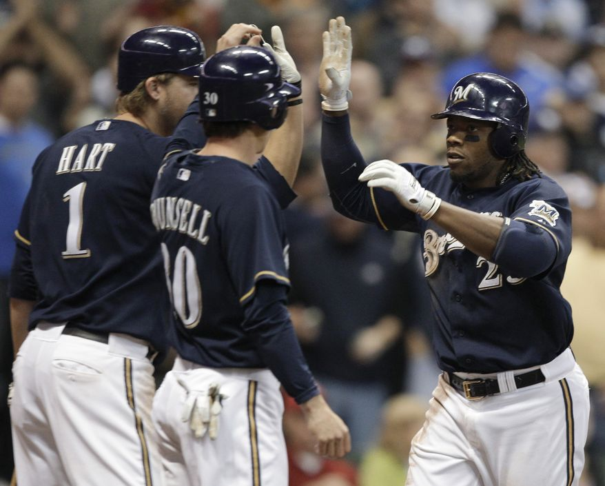 Milwaukee Brewers' Rickie Weeks (23) is congratulated by Craig Counsell and Corey Hart (1) after Weeks hit a two-run home run during the seventh inning of a baseball game against the Washington Nationals on Tuesday, May 24, 2011, in Milwaukee. (AP Photo/Morry Gash