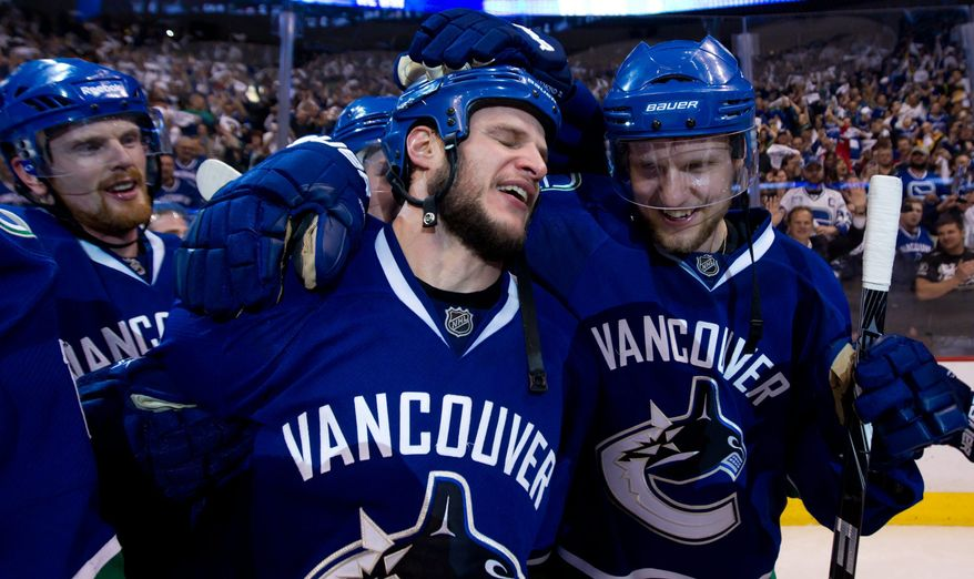 NHL Playoffs: Vancouver Canucks' Kevin Bieksa, center, who scored the game-winning goal, Alexander Edler, right, of Sweden, and Daniel Sedin, left, of Sweden, celebrate after defeating the San Jose Sharks in the second overtime period of game 5 of the NHL Western Conference Final Stanley Cup playoff hockey series in Vancouver, British Columbia, on Tuesday May 24, 2011. Vancouver won the series 4 games to 1 and advances to the Stanley Cup Final. (AP Photo/THE CANADIAN PRESS/Darryl Dyck)