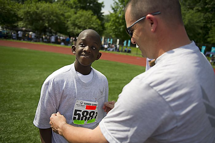 Javon McCray (left) gets his Air Force tee shirt put on by Air Force Senior Master Sgt. Steven Mandell (right) prior to the running of the Unified 4x100 meter relay, during the 2011 Special Olympics D.C. Summer Games being held at Catholic University in Washington, D.C., Wednesday, May 25, 2011. (Rod Lamkey Jr./The Washington Times)
