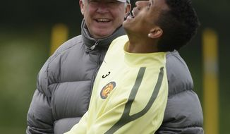 Manchester United's manager Alex Ferguson  watches as Nani heads the ball during a training session at Carrington training ground in Manchester, Tuesday, May 24, 2011. Manchester United will play Barcelona in the Champion's League final soccer match Saturday. (AP Photo/Jon Super)