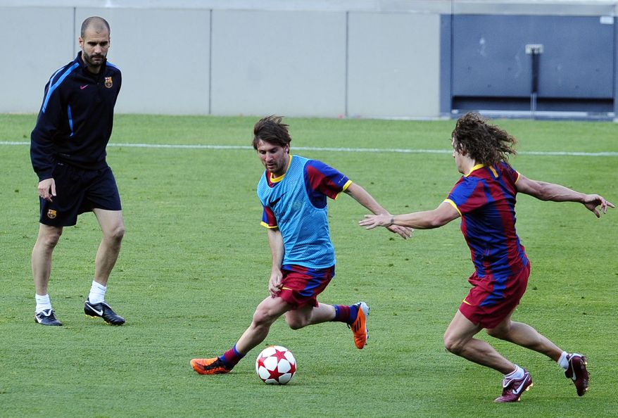 FC Barcelona's coach Pep Guardiola, left, Lionel Messi, from Argentina, center, and Carles Puyol attend a training session at the Camp Nou stadium in Barcelona, Spain, Monday, May 23, 2011. FC Barcelona will play against Manchester United in the final of the Champions League at Wembley stadium in London on May 28. (AP Photo/Manu Fernandez)