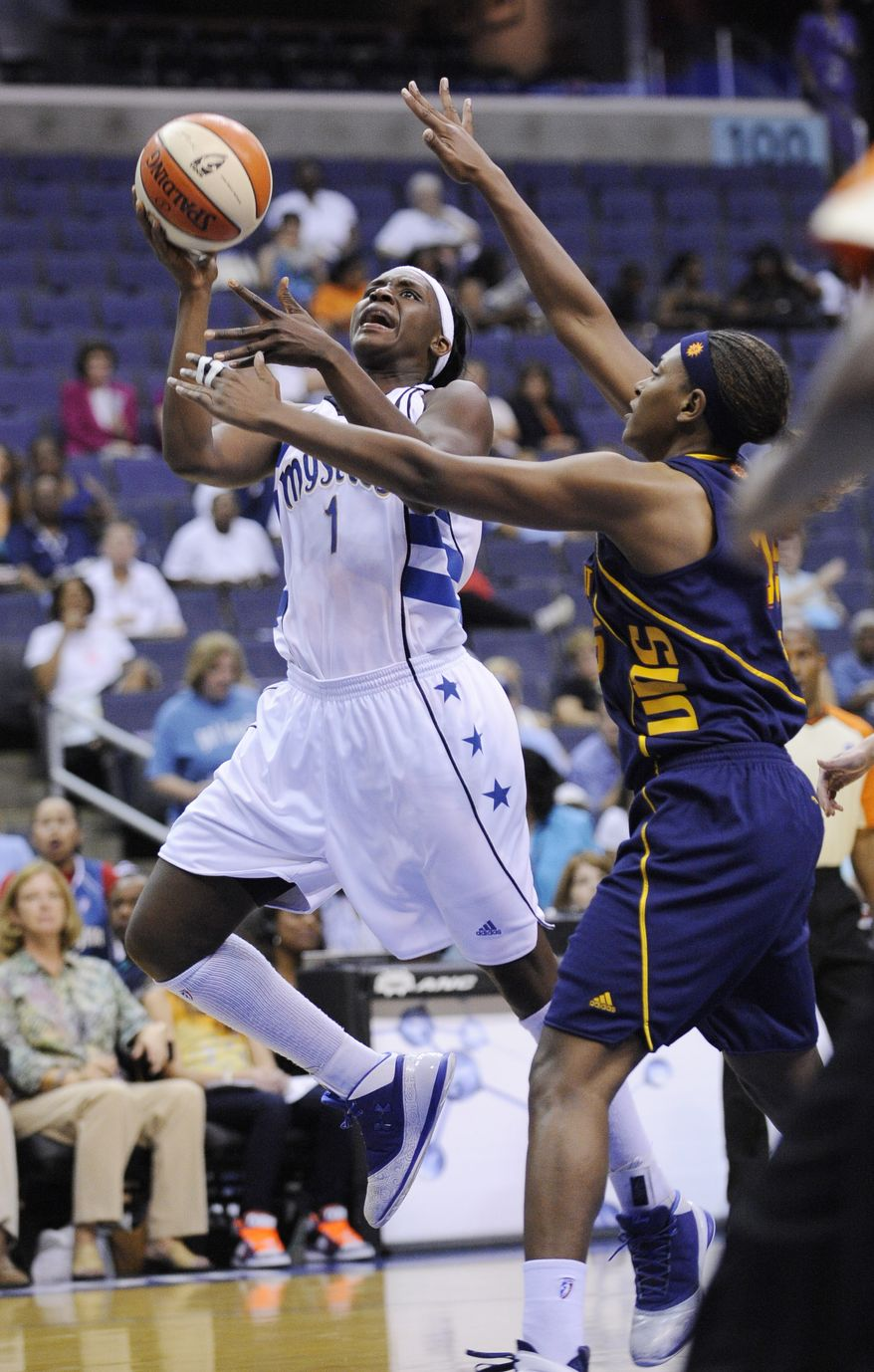 Washington Mystics' Crystal Langhorne (1) goes to the basket against Connecticut Sun's Asjha Jones, right, during the first half of an WNBA basketball game in 2010. Langhorne led all scorers in Thursday morning's exhibition game against the Chicago Sky with 15 points and nine rebounds. The Mystics won 66-55.