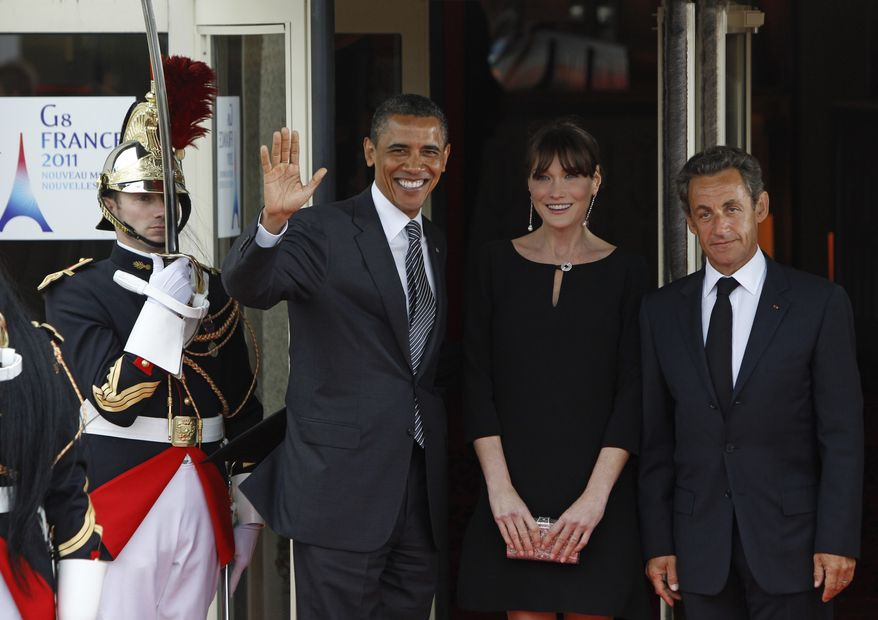 French President Nicolas Sarkozy (right) and his wife, Carla Bruni-Sarkozy (center), welcome President Obama to Le Ciro's Restaurant during a dinner meeting for the G8 summit in Deauville, France, on May 26, 2011. (Associated Press)