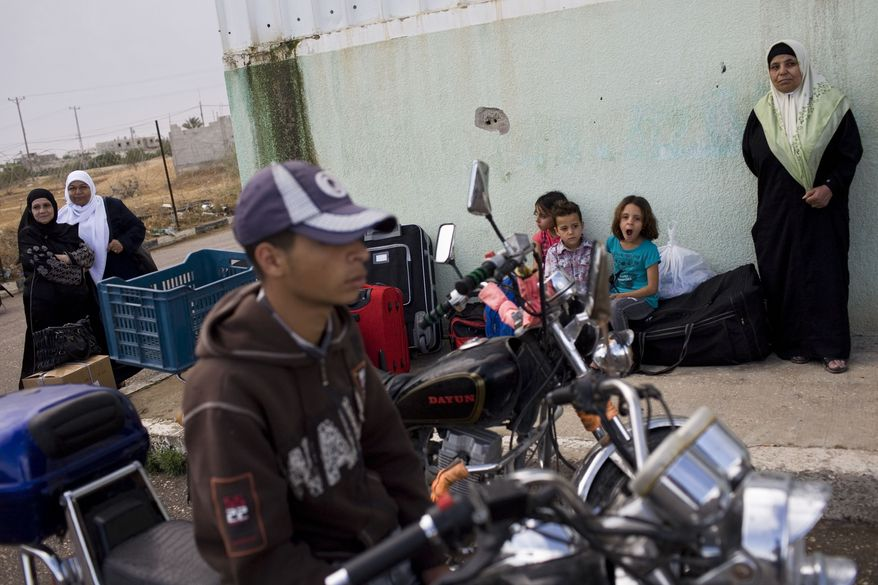 Palestinians wait before crossing into Egypt through the Rafah border crossing, southern Gaza Strip, Saturday, May 28, 2011. After four years, Egypt on Saturday permanently opened the Gaza Strip's main gateway to the outside world, bringing long-awaited relief to the territory's Palestinian population and a significant achievement for the area's ruling Hamas militant group. (AP Photo/Bernat Armangue)