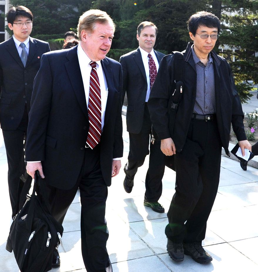 Robert King, left, U.S. special envoy for North Korean human rights issues, and U.S. citizen Eddie Jun, right, prepare to leave Pyongyang, North Korea, on Saturday May 28, 2011. (AP Photo/Kyodo News)