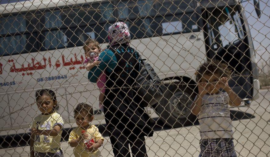 A Palestinian family waits before crossing into Egypt through the Rafah border crossing, southern Gaza Strip, Saturday, May 28, 2011. (AP Photo/Bernat Armangue)