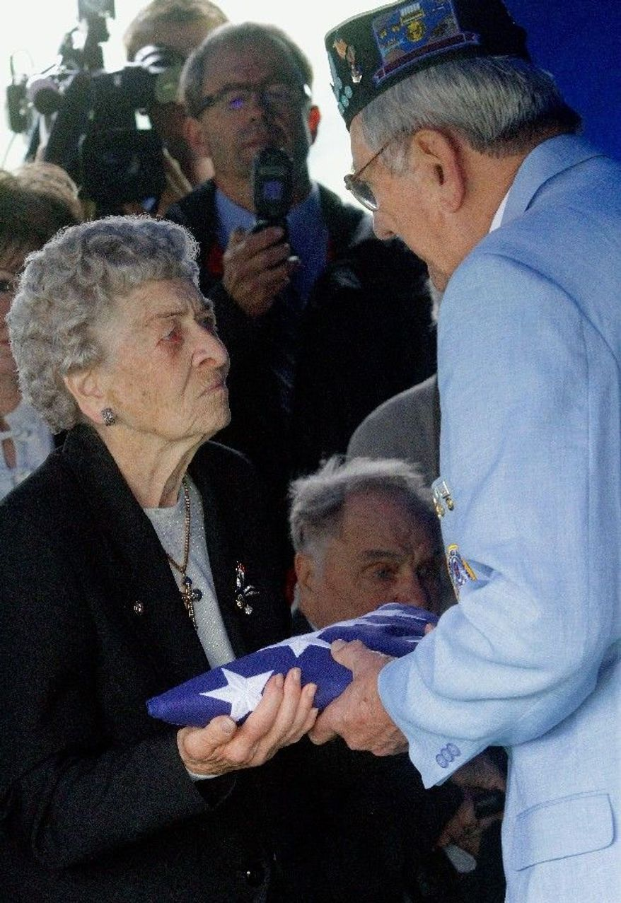 Frances Meyers, 88, receives the flag that covered her brother Artie Hodapp's casket from Korean War veteran Dwight Allmon during services in Freeport, Ill., on Wednesday. (Associated Press)