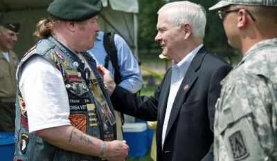 """Secretary of Defense Robert M. Gates pats Army veteran Craig Gerhartz on the back prior to speaking at the Rolling Thunder rally Sunday. Mr. Gerhartz, from South River, N.J., served in the Army during the Vietnam War. Mr. Gates gave him two military """"challenge coins."""" (Drew Angerer/The Washington Times)"""