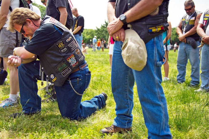 Paul Kocic, who served in the U.S. Army from 1973 to 1998, bows his head during a moment of silence for fallen troops at the Rolling Thunder motorcycle rally on Sunday. Mr. Kocic said he comes to event, which honors American veterans and prisoners of war, every year. (Drew Angerer/The Washington Times)