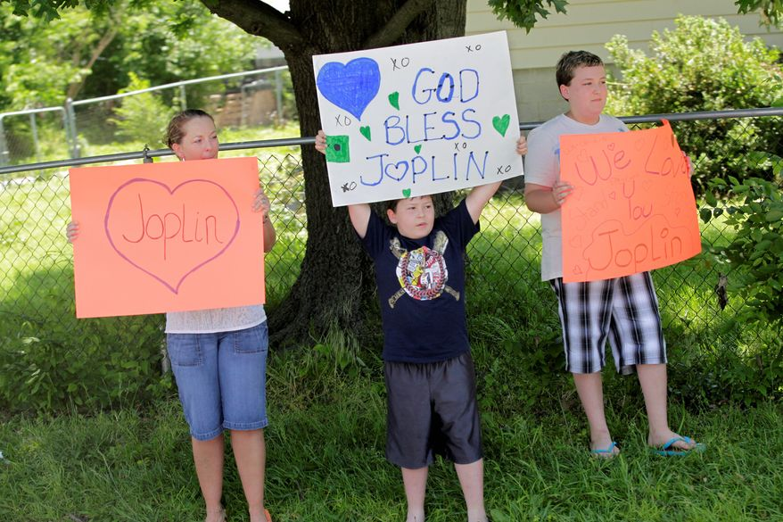 """Residents of Joplin, Mo., hold up signs of encouragement for their ravaged city during a visit Sunday from Mr. Obama. The president told Missouri Gov. Jay Nixon he'll help cut through """"red tape"""" so federal aid can flow quickly to Joplin."""