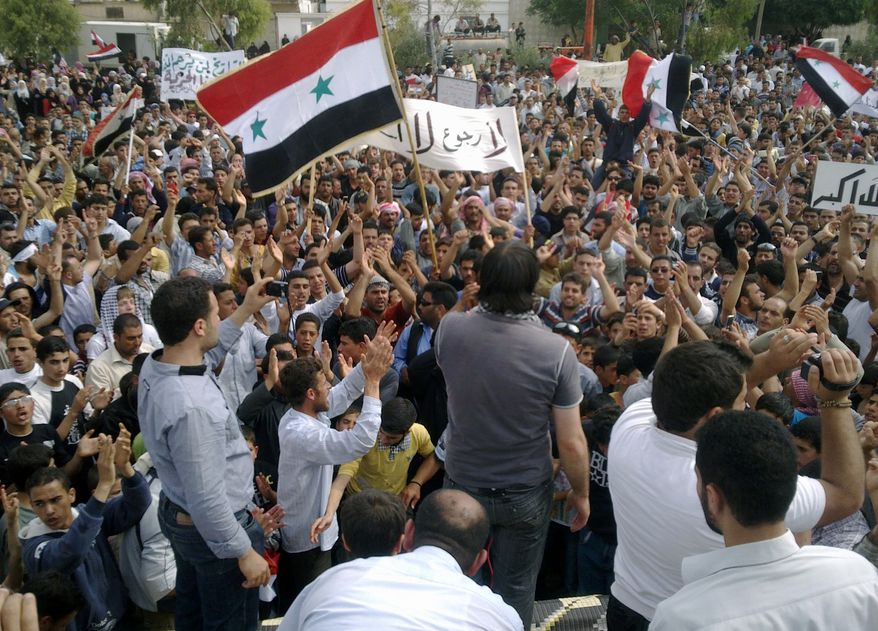 Syrian anti-regime protesters carry national flags and banners during a rally in Talbiseh, in the central province of Homs, Syria, on Friday, May 27, 2011, in this image taken by a citizen journalist on a cellphone camera  provided by Shaam News Network on Sunday. (AP Photo/Shaam News Network)