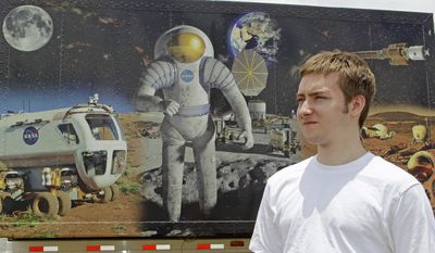 John Burnham, one of two dozen recipients of a unique scholarship, walks past a space mural at the Kennedy Space Center Visitor Complex in Cape Canaveral, Fla. John is being paid not to go to college and instead will work on an ambitious science project involving building mines on asteroids. (Associated Press)
