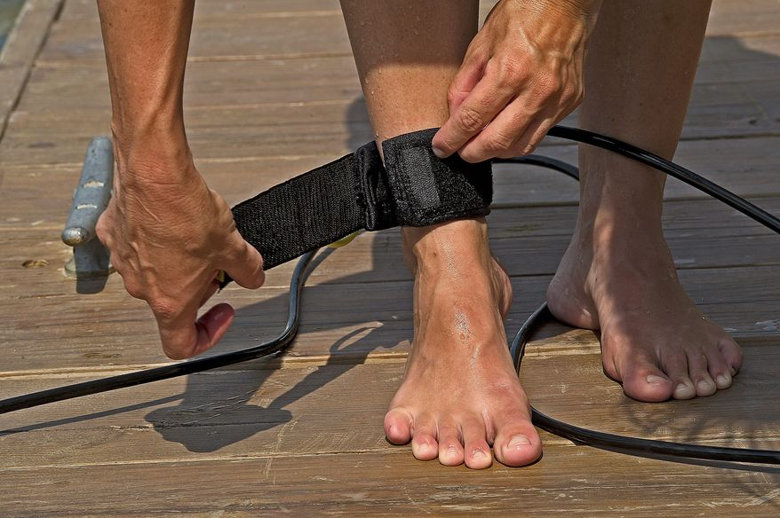 A paddle boarder wraps the ankle strap from the board around her ankle before heading out to paddle on the Potomac River. By law, paddle boarders must either wear a life vest or have one accessible on a vessel. (Barbara L. Salisbury/The Washington Times)