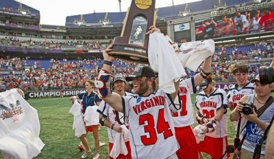 Colin Briggs hoists the trophy after the University of Virginia Cavaliers' 9-7 victory over the rival Maryland Terrapins for the NCAA lacrosse championship, played at M&T Bank Stadium in Baltimore. (Rod Lamkey Jr./The Washington Times)