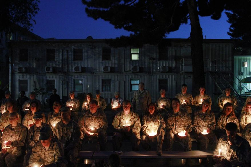 U.S. soldiers holds candles to mark Memorial Day at the headquarters of the U.S. Army Corps of Engineers in Kabul, Afghanistan, on Sunday, May 29, 2011. (AP Photo/Musadeq Sadeq)