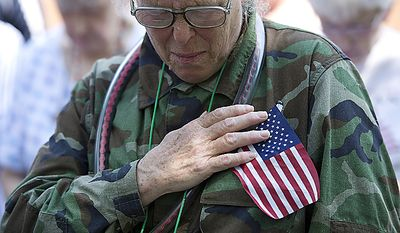 Kristin Krombein of Falls Church, Va., holds her hand over her heart during the singing of the national anthem at the Falls Church City Memorial Day Veteran's Ceremony in Falls Church, Va., on Monday, May 30, 2011. Krombein says she wore the camouflage outfit to honor the Vietnam vet who asked her to marry him following his return from the war. Although she broke off the engagement, she says that she still wears the uniform to honor him and the other Marines who are still fighting. (Barbara L. Salisbury/The Washington Times)