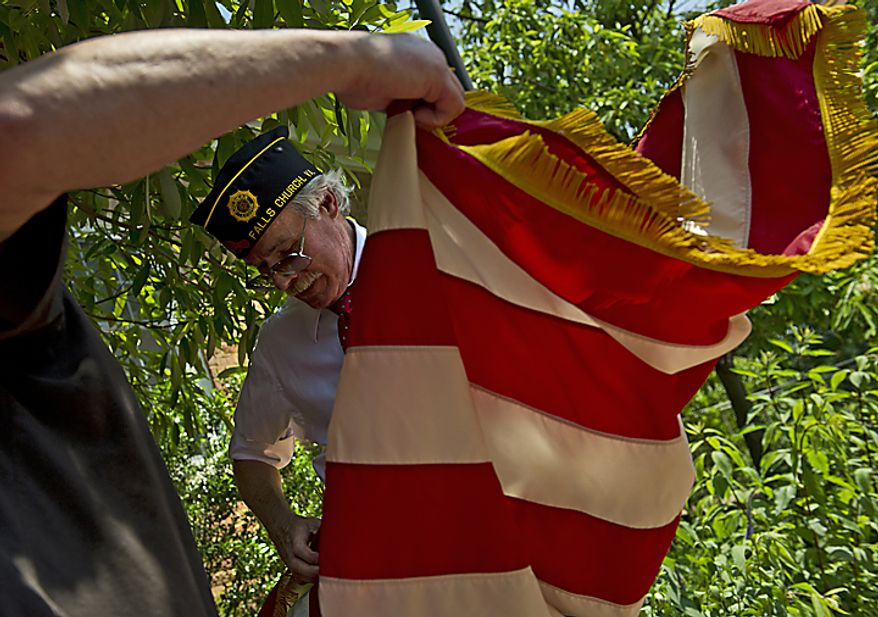 John D. Johnson, incoming commander of American Legion Post 130, of Falls Church, Va., gets help folding up the American flag following the Memorial Day Veteran's Ceremony in Falls Church City, Va., on Monday, May 30, 2011. (Barbara L. Salisbury/The Washington Times)