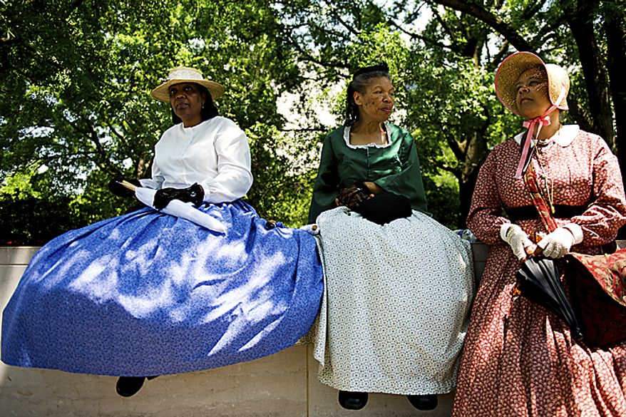 """From left, Helen Hassell, Pat Tyson and Judy Williams, wear their Civil War era clothing as they wait for the National Memorial Day Parade to start, near the National Mall in Washington, D.C., Monday, May 30, 2011. The women are with the group """"FREED"""" - Female Re-enactors of Distinction, from the African-American Civil War Memorial and Museum in D.C. (Drew Angerer/The Washington Times)"""