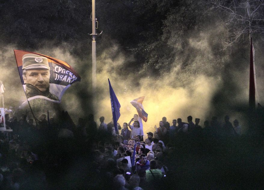 Smoke from flares engulf demonstrators during a rally in support of war crimes suspect Ratko Mladic, seen on the flag at left, in Belgrade, Serbia, on Sunday, May 29, 2011. Mr. Mladic was arrested on Thursday after 16 years on the run. (AP Photo/Vadim Ghirda)