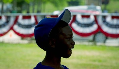 Kwon Holes, 11, watches the speakers Tuesday during the Washington Nationals Youth Baseball Academy groundbreaking ceremony at Fort DuPont Park in Southeast. (Rod Lamkey Jr./The Washington Times)