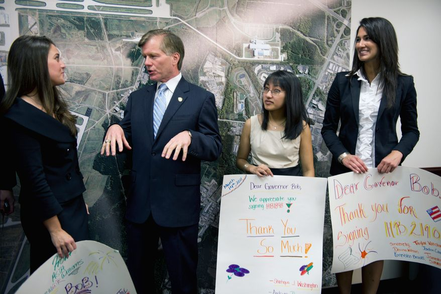 Virginia Gov. Robert F. McDonnell speaks with representatives from the Richmond Justice Initiative, including (from left) Nicole LeBoeuf, a regent law intern, Tran Doan, an administrative volunteer, and Marie Krouse, a regent law intern, at the signing of sex trafficking legislation Tuesday. (Barbara L. Salisbury/The Washington Times)