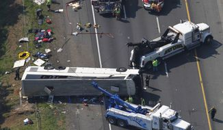 Rescue personnel work on a bus that overturned on Tuesday, May 31, 2011, in Bowling Green, Va. The commercial tour bus went off Interstate 95 and flipped on its roof before dawn, killing four people and injuring many more, Virginia State Police said. (AP Photo)
