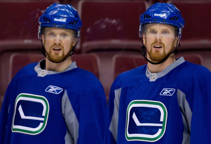 Stanley Cup: Vancouver Canucks' Henrik Sedin, left, and his twin brother Daniel Sedin, of Sweden, look on during NHL hockey practice in Vancouver, British Columbia, on Saturday, May 28, 2011. The Canucks and the Boston Bruins are scheduled to play Game 1 of the Stanley Cup final on Wednesday. (AP Photo/The Canadian Press, Darryl Dyck)