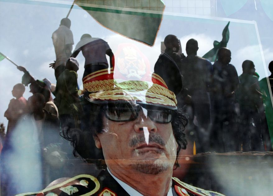 ASSOCIATED PRESS Col. Moammar Gadhafi's portrait hangs behind a window that reflects people gathering this week at the dictator's Bab al-Aziziya compound, a regular target of NATO airstrikes in Tripoli, Libya.