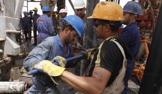 Oil workers work at Zubair oil field near Basra, 340 miles southeast of Baghdad, Iraq, Sunday, May 15, 2011. (AP Photo/Nabil al-Jourani) ** FILE **