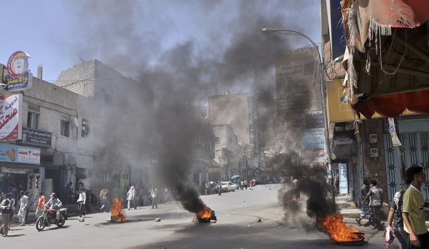 Burning tires left by anti-government protesters block the road during clashes between the protesters and Yemeni security forces in Taiz, Yemen, on May 31, 2011. (Associated Press)