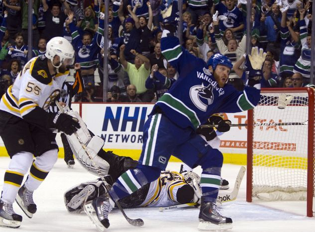 Vancouver Canucks left wing Raffi Torres celebrates after scoring the winning goal against Boston Bruins goalie Tim Thomas as Boston Bruins defenseman Johnny Boychuk looks on during the third period of game one Stanley Cup final playoff hockey action in Vancouver, British Columbia, Wednesday, June 1, 2011. (AP Photo/The Canadian Press, Darryl Dyck)