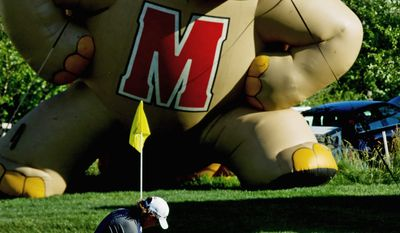 DREW ANGERER/THE WASHINGTON TIMES With an inflatable University of Maryland Terrapin looming over the green, Greg Owen makes a chip shot on the 18th hole during the first round of the Prince George's County Open. The Nationwide Tour event is being held at the University of Maryland Golf Course in College Park.