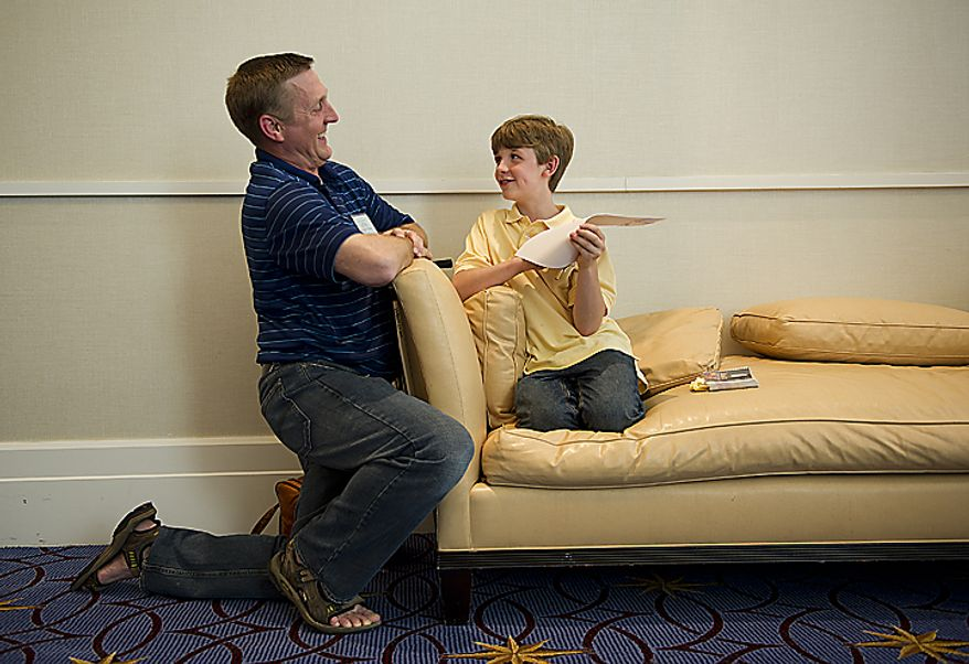 Speller Lucas Urbanski, 11, of Crystal Lake, Illinois, hangs out with his dad Michael in the lobby outside the Maryland Ballroom at the Gaylord National in Oxon Hill, Md., following Round Three of the 2011 Scripps Howard National Spelling Bee on Wednesday, June 1, 2011. Lucas says he got four wrong on the written test but didn't miss any words in the oral competition, so now he must wait and see if he is one of the 50 spellers who will move on to Thursday's semifinals. (Barbara L. Salisbury/The Washington Times)