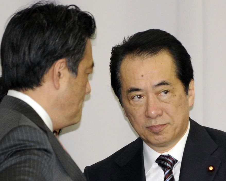 Japanese Prime Minister Naoto Kan (right) talks with Katsuya Okada, secretary-general of the ruling Democratic Party of Japan, at a meeting of the party's members of parliament on Thursday, June 2, 2011, in Tokyo. (AP Photo/Kyodo News)