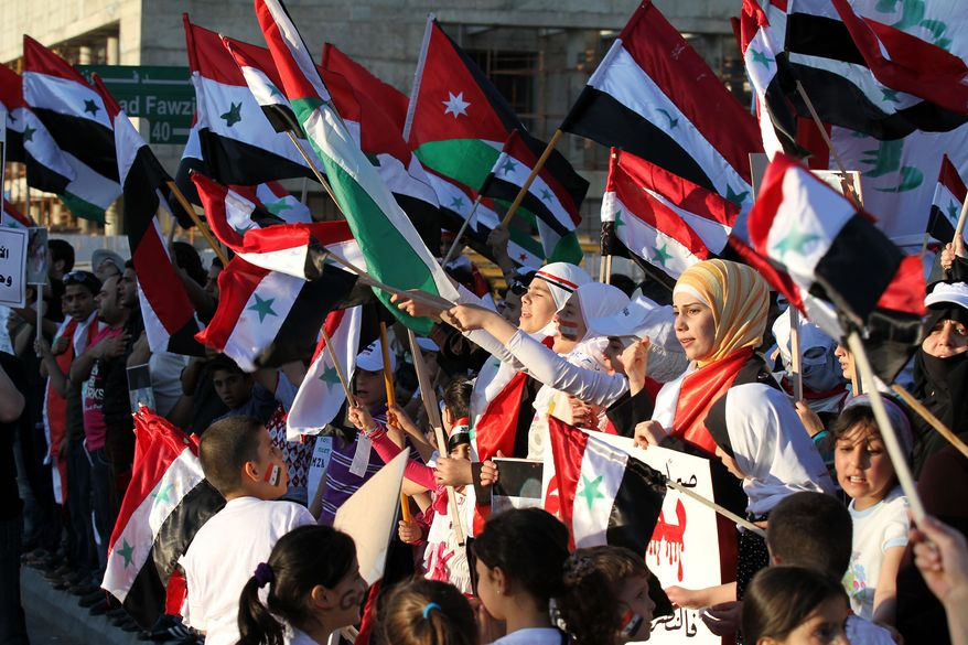Syrian protesters carry national flags during a rally near the Syrian Embassy in Amman, Jordan, on Wednesday, June 1, 2011, as they demand that Syrian President Bashar Assad step down. (AP Photo/Nader Daoud)