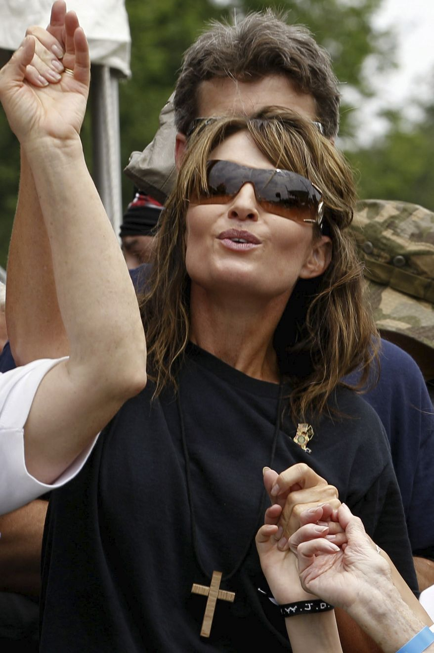 Former Alaska governor and vice presidential candidate Sarah Palin holds hands with people gathered for Memorial Day weekend events on the National Mall in Washington on May 29, 2011. Palin rode to the mall from the Pentagon with motorcyclists in the traditional annual Rolling Thunder rally. (Associated Press)