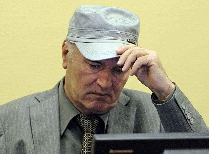 Former Bosnian Serb Gen. Ratko Mladic removes his hat in the courtroom during his initial appearance at the Yugoslav war crimes tribunal in The Hague on Friday, June 3, 2011. (AP Photo/Martin Meissner, Pool)