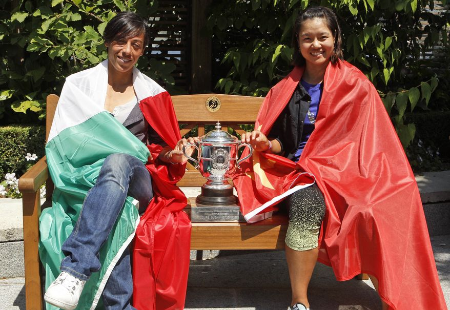 Clad in their respective national flags, the two finalists of the women's singles Francesca Schiavone of Italy, left, and Li Na of China, right, pose with the trophy one day before the women's final during a photo opportunity at the French Open tennis tournament in Roland Garros stadium in Paris, Friday, June 3, 2011. (AP Photo/Lionel Cironneau)