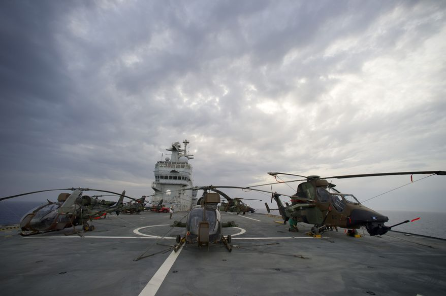 Combat helicopters are readied on the deck of the French navy vessel BPC Tonnerre in the Mediterranean Sea on Saturday, June 4, 2011, before British Apache and French attack helicopters struck targets for the first time in NATO's campaign in Libya. (AP Photo/Arnaud Roine/ECPAD)
