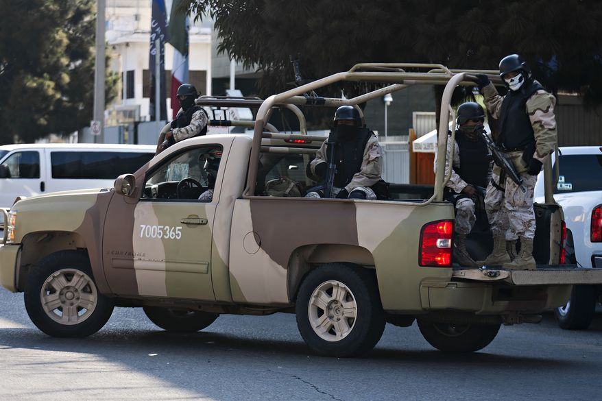 Mexican army soldiers guard the perimeter around the regional Attorney General's office after the early morning arrest of former Tijuana Mayor Jorge Hank Rohn in the city of Tijuana, Mexico, Saturday June 4, 2011. (AP Photo/Francisco Vega)