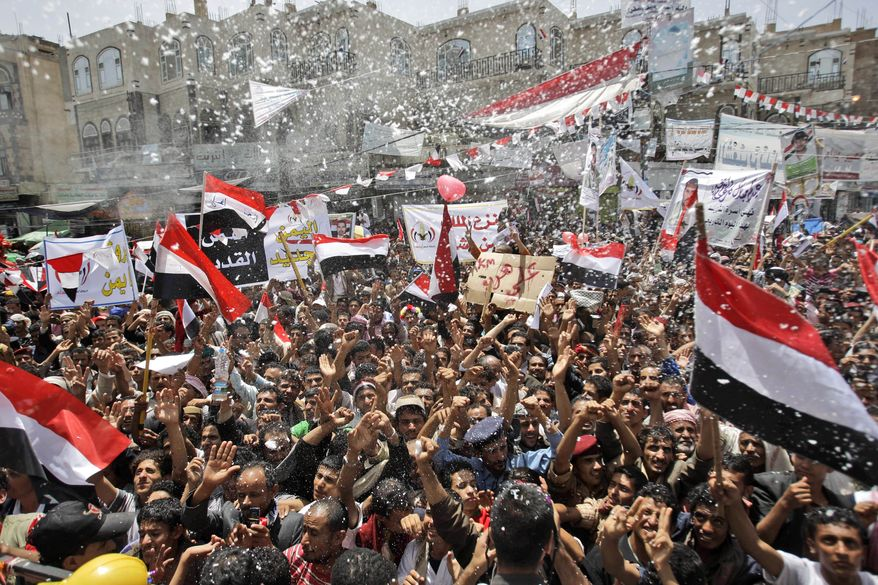 Yemeni anti-government protesters spray foam and wave their national flags in Sanaa, Yemen, on Sunday, June 5, 2011, as they celebrate President Ali Abdullah Saleh's departure to Saudi Arabia for medical treatment. (AP Photo/Hani Mohammed)