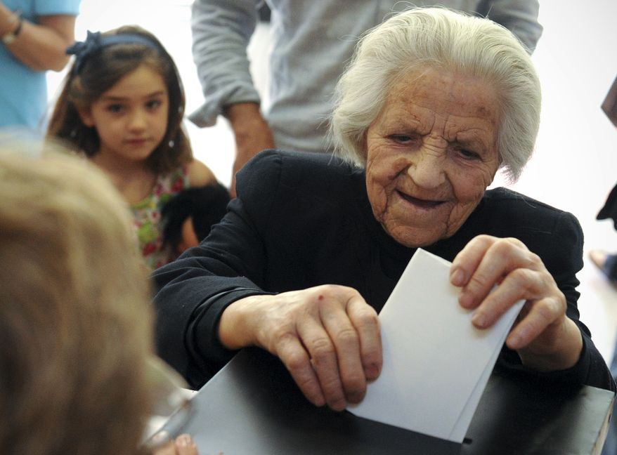 An elderly woman casts her ballot in Portugal's general election on Sunday, June 5, 2011, at a polling station in Lisbon. (AP Photo/Paulo Duarte)
