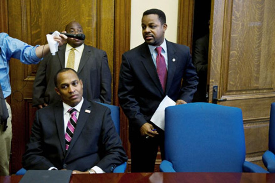 Council Chairman Kwame R. Brown (right) announces a closed-door session of council at the John A. Wilson Building on Tuesday as council member Harry Thomas Jr. sits beside him in a conference room. Mr. Brown later said that an announcement will be made Wednesday on whether Mr. Thomas faces sanctions in light a misuse of funds allegation.(DREW ANGERER/THE WASHINGTON TIMES)