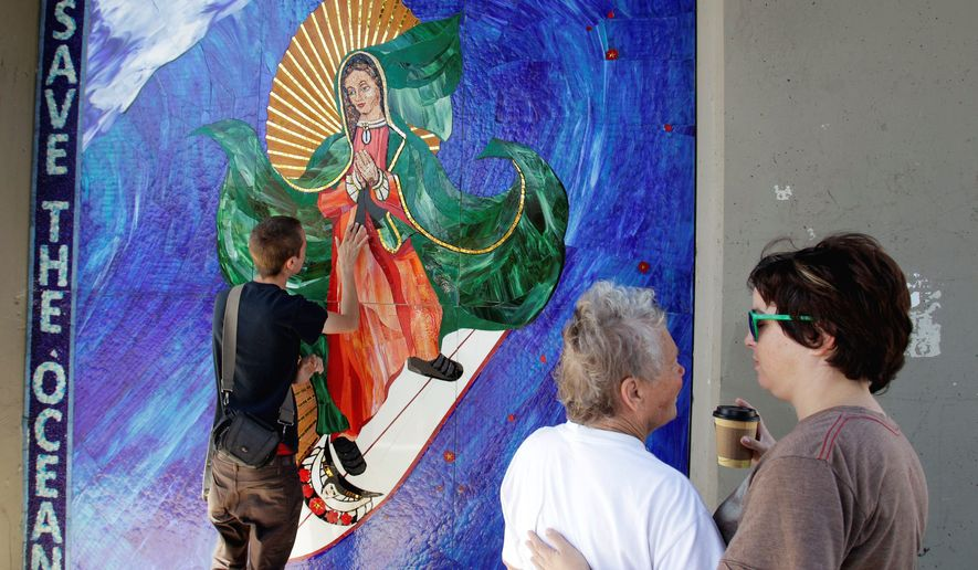 """Cincinnati artist Jules Itzkoff (left) says the image of the Virgin of Guadalupe riding a surfboard is """"so beautiful and so different that it doesn't resemble what we normally think of as graffiti."""" (Associated Press)"""