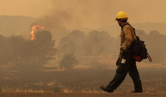 Firefighter Rigoberto Torres, of Orange Cove, Calif., walks along the road while watching a flame during the Wallow fire in the Apache-Sitgreaves National Forest near Springerville, Ariz., on June 7, 2011. (Associated Press) **FILE**